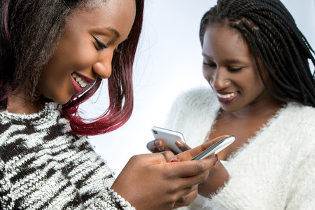 Close up portrait of two african teen girls playing on smart phones.