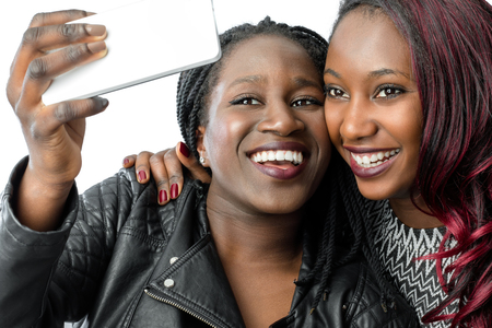 self   portrait: Close up portrait of two african teen girls taking self portrait with smartphone.Isolated on white background.