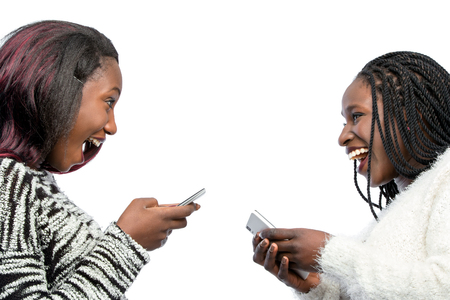 Close up portrait of happy african teen girls laughing with smart phones. Isolated on white background. Foto de archivo