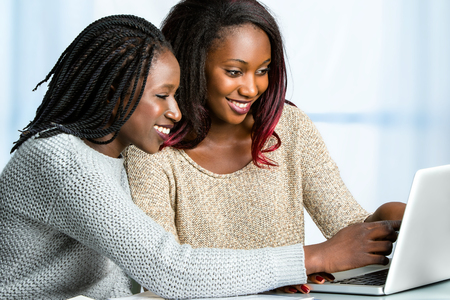 Close up portrait of two attractive african teen girls sitting together at table. Girl with braided hair pointing at computer screen.