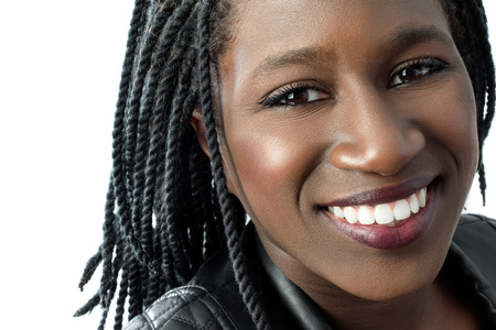 face shot: Macro close up face shot of attractive young african woman with charming smile.Isolated on white background.
