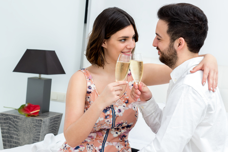 breakaway: Close up portrait of young couple toasting with champagne in hotel room. Stock Photo