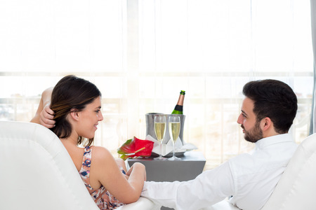 honeymoon suite: Close up portrait of young honeymoon couple in hotel suite celebrating with champagne. Stock Photo