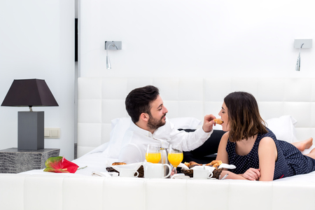 man in suite: Close up portrait of young couple having breakfast in hotel suite.