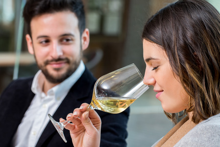 Close up portrait of young woman smelling white wine aroma at tasting. Foto de archivo