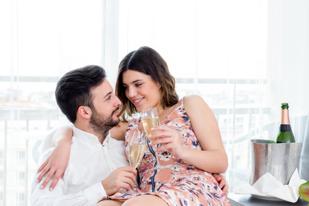 hotel suite: Close up portrait of young happy couple celebrating weekend getaway in hotel suite with champagne.