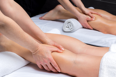 physiotherapists: Close up of physiotherapists massaging couple together in spa. Stock Photo