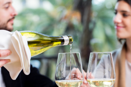 affectionate actions: Close up of waiter pouring white wine in glass with couple in background.