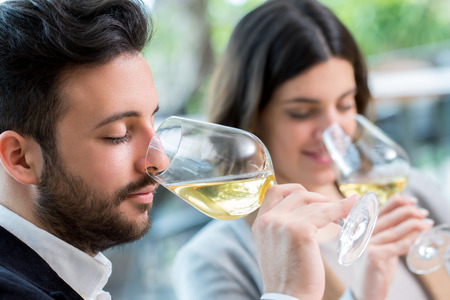 Close up portrait of young couple tasting white wine tasting. 스톡 콘텐츠