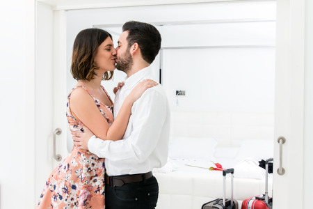 hotel suite: Close up portrait of romantic kiss in hotel suite.