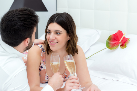 breakaway: Close up portrait of young couple drinking sparkling wine on bed in hotel room.