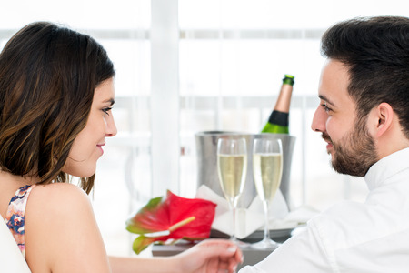 breakaway: Close up Side view portrait of romantic couple in hotel room with sparkling wine in background.