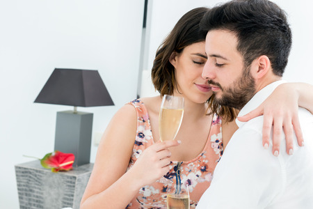 romantic room: Close up portrait of romantic couple with eyes closed in hotel room holding champagne glasses.