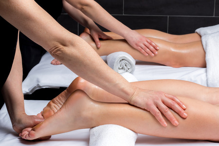 lower body: Close up of simultaneous leg massage on couple in spa.Two physiotherapists applying pressure on couples legs.