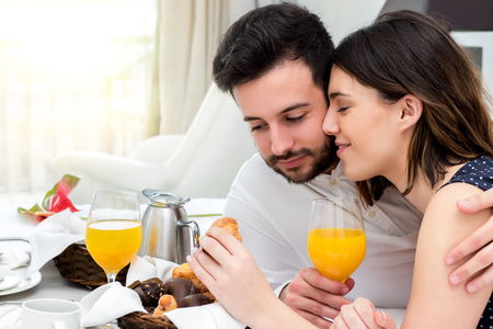 honeymoon suite: Close up portrait of young honeymoon couple enjoying room service in hotel suite.