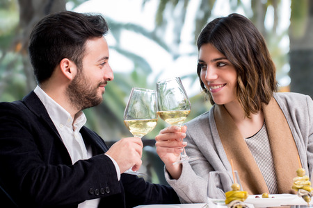 honeymoon: Close up of young handsome Couple sharing special moment white wine in restaurant.
