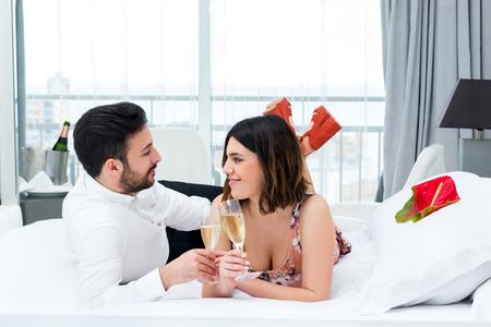 luna de miel: Cerca de retrato de joven pareja en luna de miel en hotel.Man y mujer bebiendo champán en la cama en la suite.