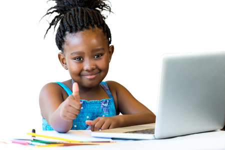 schooler: Close up portrait of cute african girl doing thumbs up at desk isolated.Isolated on white background. Stock Photo