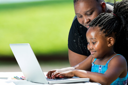 pre adult: Close up portrait of african mother supervising school work of little daughter on laptop. Cute girl typing on laptop against green background outdoors. Stock Photo