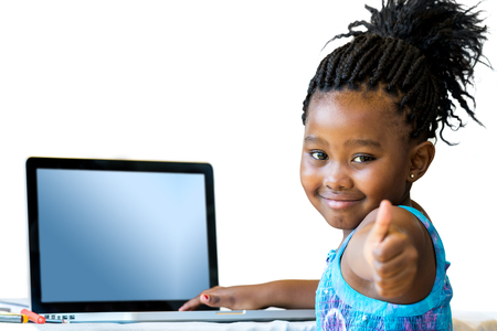 schooler: Close up portrait of cute african student with laptop doing thumbs up at desk.Isolated on white background.