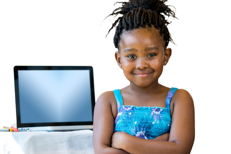 pre schooler: Close up portrait of little african kid standing with laptop in background.Isolated on white background. Stock Photo