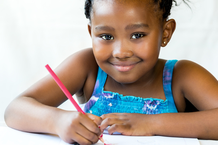 Close up face shot of african kid holding red pencil.Isolated on white background. Stock Photo
