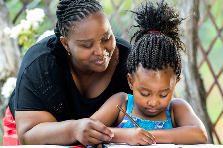 Close up portrait of african teacher supervising little kid doing homework outdoors. Stockfoto