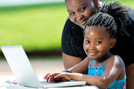 madre trabajadora: Cerca de retrato de niña africana con trenzas y madre con laptop.Kid escribiendo en la computadora portátil contra el fondo verde al aire libre. Foto de archivo