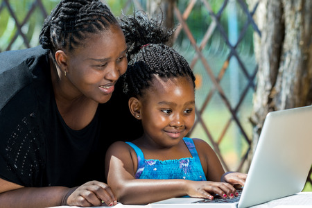 Close up portrait of African mother and little girl with braided hairstyle looking at laptop. Cute girl typing on keyboard at table in garden.