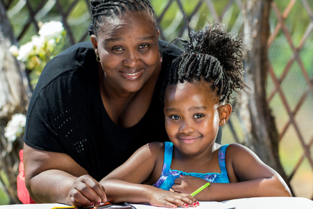femmes souriantes: Close up portrait de la mère africaine et petite fille avec coiffure tressée en garden.Girl dessin sur papier avec des crayons de couleur à l'extérieur.
