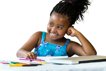schooler: Close up portrait of little african girl at desk with color pencils and laptop.Isolated on white background. Stock Photo