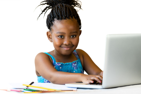 pre schooler: Close up portrait of little african girl sitting at desk with hands on keyboard.Isolated on white background. Stock Photo