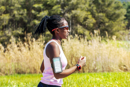 action shot: Action shot of young african woman jogging with smart watch and smart phone. Attractive teen tracking activity with fitness application.