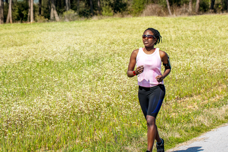 american sport: Action shot of young african woman doing exercise in countryside.Teen girl wearing smart phone on arm band and smart watch for activity tracking.