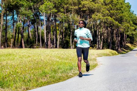 negras africanas: Toma de acción de la mujer africana joven con trenzas que activa en el camino del alquitrán en el campo verde.
