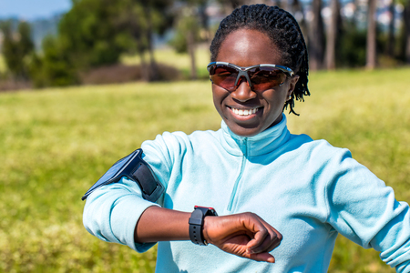 afro american: Close up portrait of young afro american woman in sportswear.Girl standing outdoors with smart phone and smart watch to track activity. Stock Photo