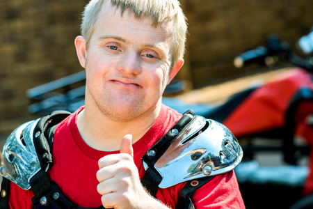 Close up portrait of young quad bike rider with down syndrome doing thumbs up.