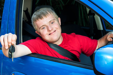 disadvantaged: Close up portrait of young car driver with down syndrome showing car keys. Young man sitting behind steering wheel with safety belt fastened.
