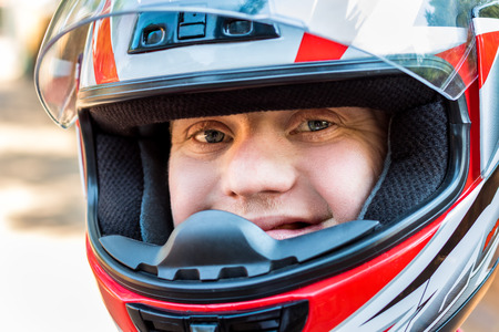 face shot: Close up face shot of young sportsman with down syndrome wearing helmet.
