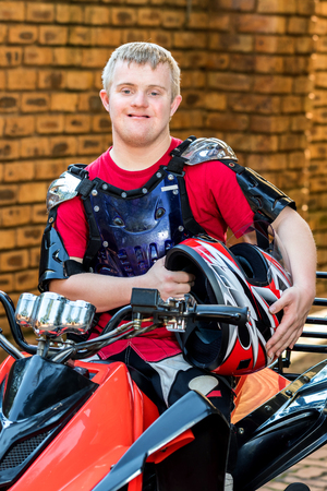 challenged: Close up portrait of young man with down syndrome sitting with sportswear and helmet on quad bike. Stock Photo