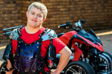 disadvantaged: Close up portrait of young handicapped sportsman standing in front of quad bike.