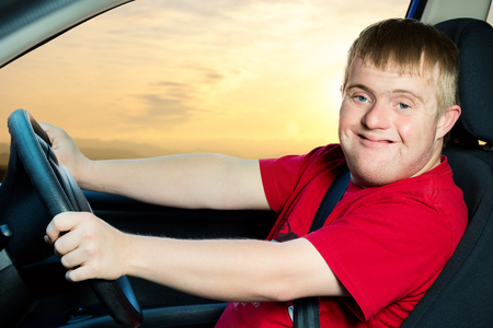 disadvantaged: Close up portrait of young man with down syndrome driving vehicle at sunset.