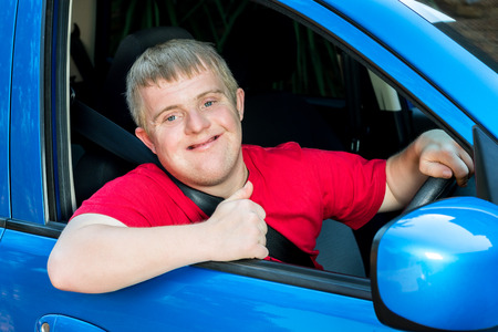 disadvantaged: Close up portrait of young handicapped car driver sitting behind steering wheel doing thumbs up symbol. Stock Photo