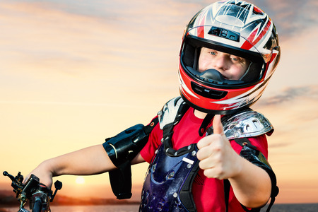 Close up portrait of young quad bike rider with down syndrome doing thumbs up on bike. Stock Photo
