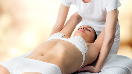 manipulating: Close up of young woman receiving osteopathic massage. Therapist manipulating arms and shoulder blades.