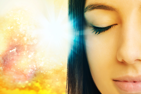 Macro close up of young woman meditating with eyes closed.Conceptual spiritual background with light beam.