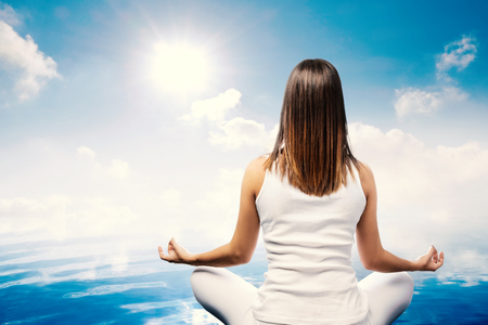 body scape: Close up rear view of young woman meditating at water side. Girl in white sitting looking at sun and clouds.