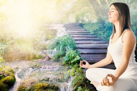 esoterismo: Cierre de vista lateral de la mujer joven en la meditaci�n pr�ximo blanco para transmitir en forest.Girl sentado en camino de madera junto al lado del agua.