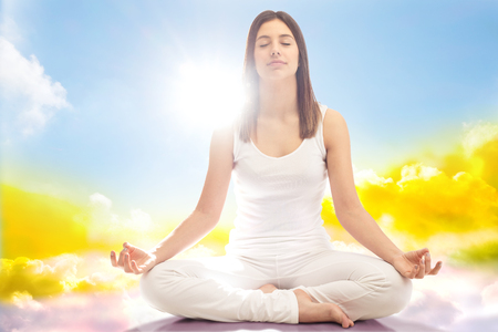 Close up full length portrait of young woman dressed in white meditating with eyes closed.Girl sitting in yoga position surrounded by clouds.