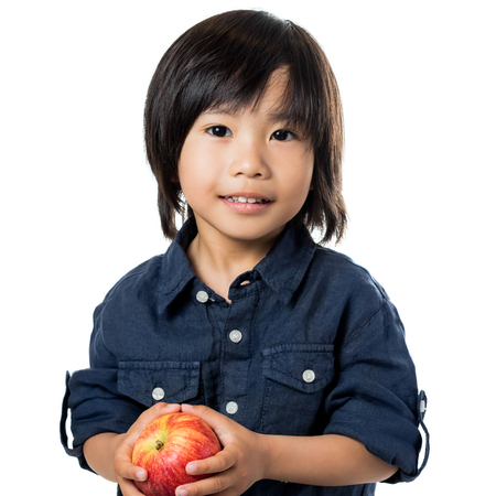 asian boy: Close up portrait of little asian boy holding red apple.Isolated on white background.